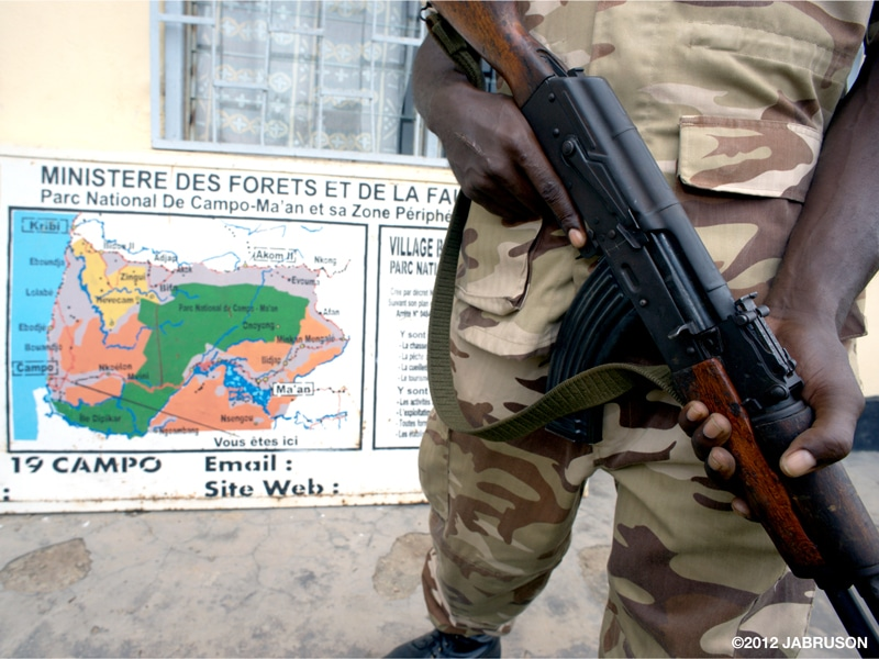 A person in a Campo Ma'an National Park, Cameroon, ranger uniform holds a long gun with a map in the background and French writing